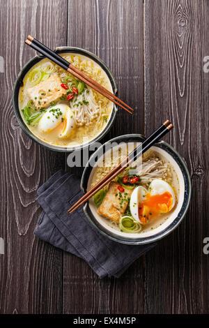 Nouilles ramen Miso asiatique avec des œufs, tofu et enokis dans des bols sur fond de bois gris Banque D'Images