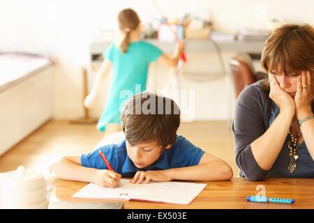 Mère et fils faire ses devoirs à la table de cuisine, la fille en arrière-plan Banque D'Images
