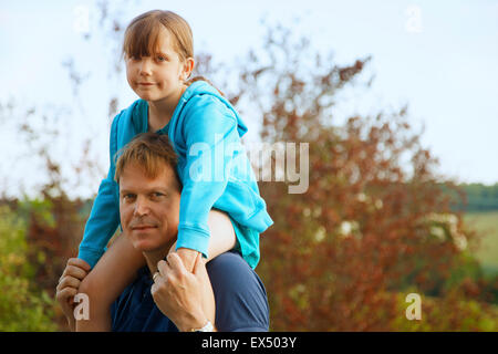 Father Carrying Daughter on Shoulders Outdoors Banque D'Images