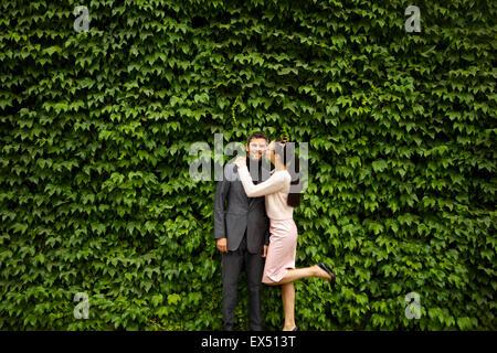 Woman Kissing Man on joue en face de couverture vert foncé Banque D'Images