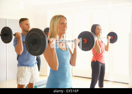 Trois personnes le Barbell de levage au cours de conditionnement physique Banque D'Images