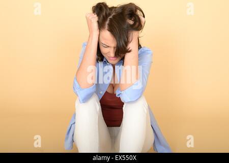 Attrayant beau triste déprimé et en colère jeune femme assise sur le sol portant une chemise bleu et blanc jeans Banque D'Images