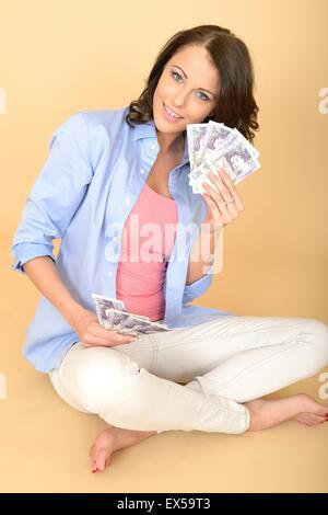 Attractive Young Woman Holding une poignée de 20 livres en argent comptant ou des notes à heureux et ravis seul Banque D'Images