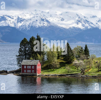Maison rouge typique sur une île dans le Hardangerfjord, près de Strandebarm, Hordaland, Norvège Banque D'Images