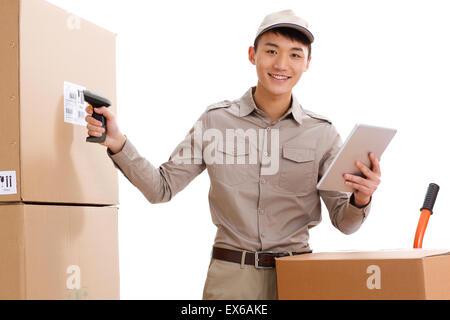 Jeune homme la numérisation des boîtes avec lecteur de code à barres Banque D'Images