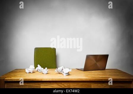 Image d'un bureau vide avec une chaise, un ordinateur portable et des papiers froissés sur le bureau Banque D'Images