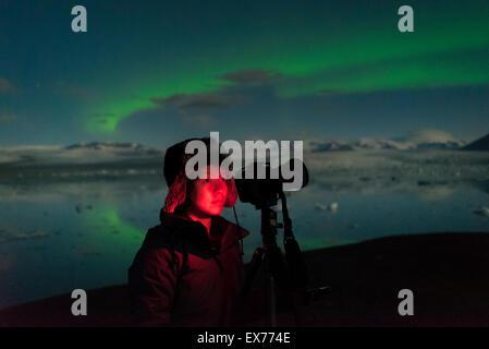 Femme à prendre des photos de l'Aurore boréale au Jokulsarlon Glacial Lagoon, Iceland. Banque D'Images