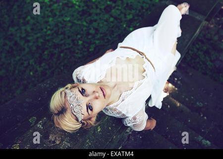 Jeune femme se trouve en haut des escaliers sur robe blanche dans le bois Banque D'Images