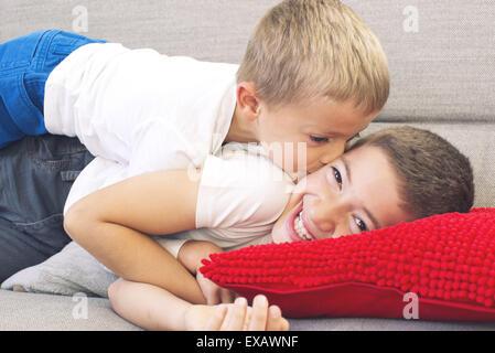 Petit garçon embrassant la joue de son frère aîné Banque D'Images