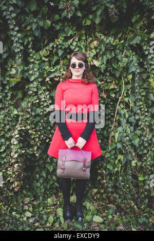 ... Belle jeune femme hipster vintage rouge habillé en street town Banque  D Images f3e26aca159