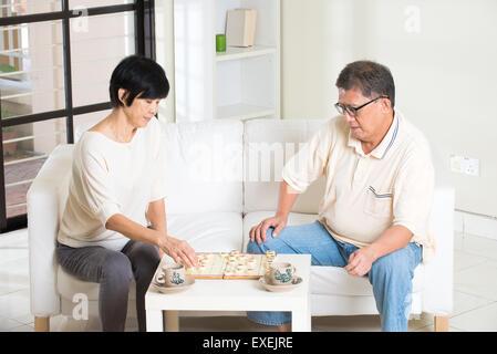 Asian senior couple jouant aux échecs à la maison Banque D'Images