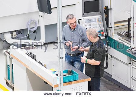 Les travailleurs d'usine en usine discussion ayant workstation Banque D'Images