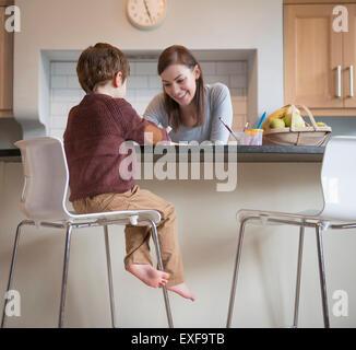 Garçon assis sur la selle avec la mère dans la cuisine et le dessin Banque D'Images