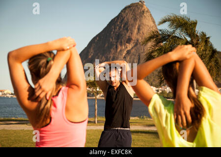 Deux amies exerçant en parc avec entraîneur personnel, Rio de Janeiro, Brésil Banque D'Images
