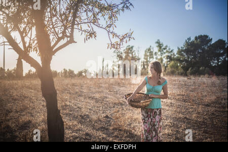 Mature Woman holding basket in orchard Banque D'Images