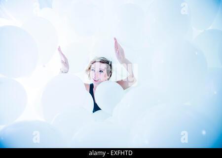 Globophobia: a happy smiling young woman girl seul dans un nuage de centaines de ballons blancs - après avoir surmonté sa peur irrationnelle de ballons