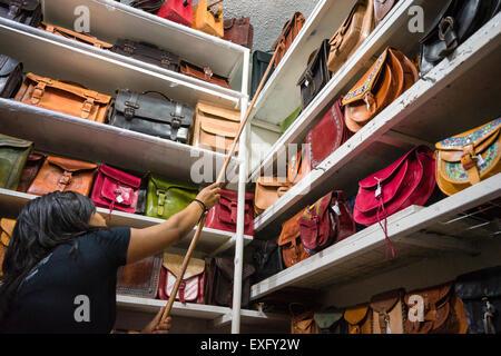 Une femme ayant atteint de sac à main en cuir à partir de la tablette du haut dans un étal dans un marché à Oaxaca, Banque D'Images