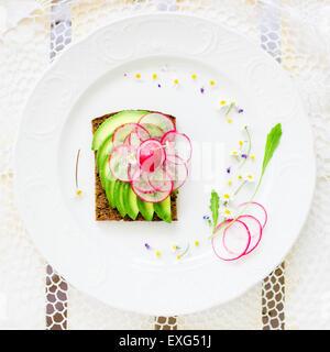 Sandwich à l'avocat végétalien décoré de tranches de radis frais. Vue d'en haut Banque D'Images