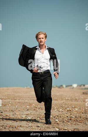 Homme dans un costume noir à courir après quelqu'un sur la plage tenant un pistolet. Banque D'Images