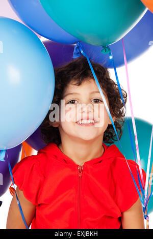 Adorable petit caucasien enfant avec des cheveux bouclés portant un haut à capuchon rouge. La fille est maintenant Banque D'Images