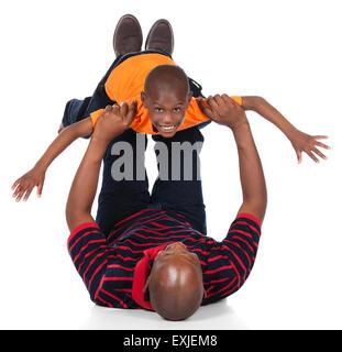 Cute african boy portant un tee-shirt orange et jeans en denim foncé joue avec son père. Banque D'Images