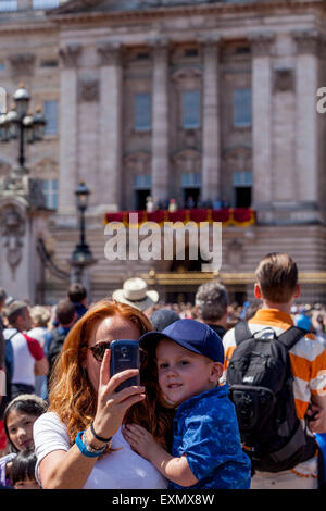 Un visiteur prend une des Selfies elle-même et enfant à l'extérieur du palais de Buckingham, Londres, Angleterre Banque D'Images
