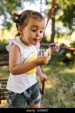 Petite fille en essayant de manger la crème glacée Banque D'Images