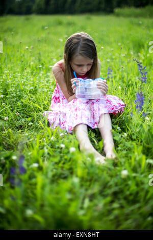 Petite fille assise sur une prairie avec insecte peut Banque D'Images
