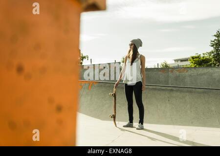 Les jeunes skate boarder portant des lunettes de soleil et le chapeau debout dans un skatepark