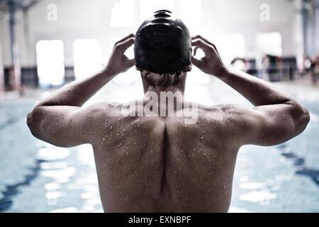 Nageur dans une piscine intérieure de mettre des lunettes swimmming Banque D'Images