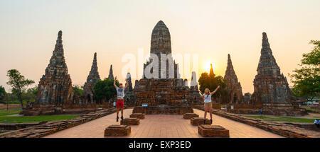 Deux touristes de sauter devant un temple bouddhiste, Wat Chaiwatthanaram, Ayutthaya, Thaïlande Banque D'Images