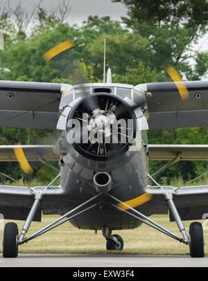 Vue de face d'un vieux biplan vintage avec rotation des hélices, en attente sur un aérodrome peu avant le départ. Banque D'Images