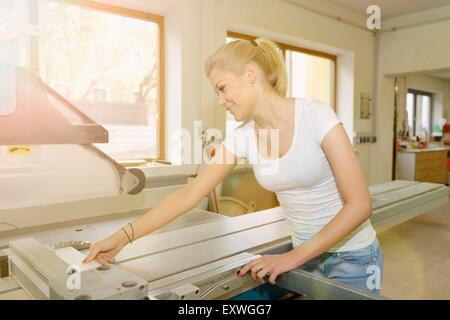 Jeune femme travaillant dans un bois sur un buzzsaw Banque D'Images
