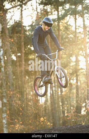 Adolescent qui saute dans l'air avec son vélo BMX Banque D'Images