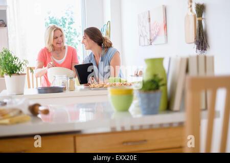 Mère avec sa fille adulte baking in kitchen Banque D'Images