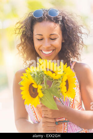 Portrait of smiling woman with sunflowers Banque D'Images