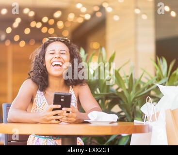 Femme à l'aide de Phone in cafe Banque D'Images