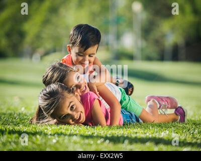 Enfants (2-3, 6-7, 8-9) playing in park Banque D'Images
