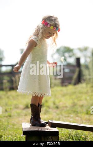 Cute girl (4-5) in white dress debout sur une clôture en prairie