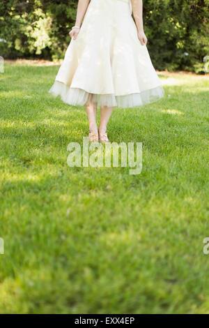 Femme en robe blanche debout sur la pelouse Banque D'Images