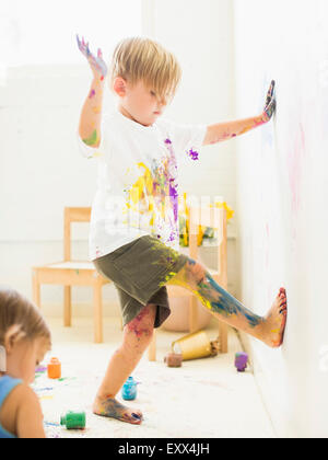 Boy (2-3) peinture sur le mur avec les mains et les jambes Banque D'Images