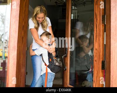 Boy (6-7) hugging mère avant de partir pour l'école Banque D'Images