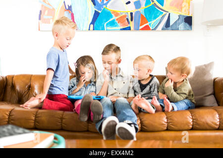 Enfants (2-3, 4-5, 6-7) sitting on sofa and using digital tablet Banque D'Images