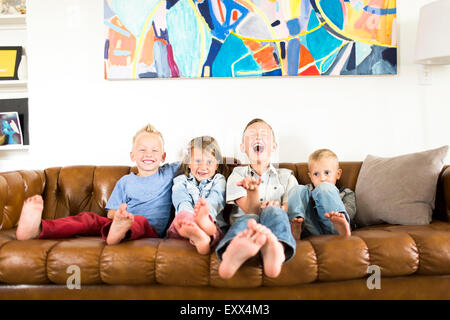 Smiling Children (2-3, 4-5, 6-7) sitting on sofa Banque D'Images