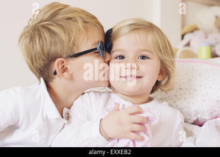 Boy kissing sister's cheek Banque D'Images