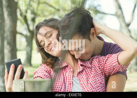 Couple embracing outdoors, selfies posant pour une Banque D'Images