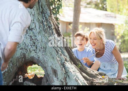 Jeune garçon et sa mère se cacher derrière arbre, jouer à cache-cache Banque D'Images