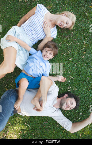 Jeune famille avec boy lying together on grass Banque D'Images