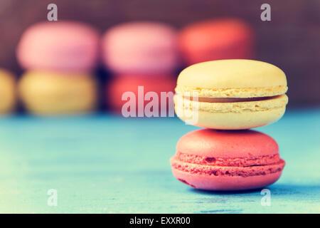 Certains macarons appétissants avec différentes couleurs et saveurs sur une surface en bois rustique bleu, croix Banque D'Images