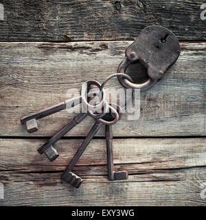 Vieux serrure rouillée avec des clés sur fond de bois. Banque D'Images